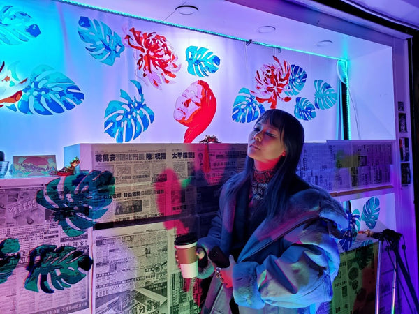 Melissa Ip poses in front of her likeness at the newsstand lantern by Prisca Choe