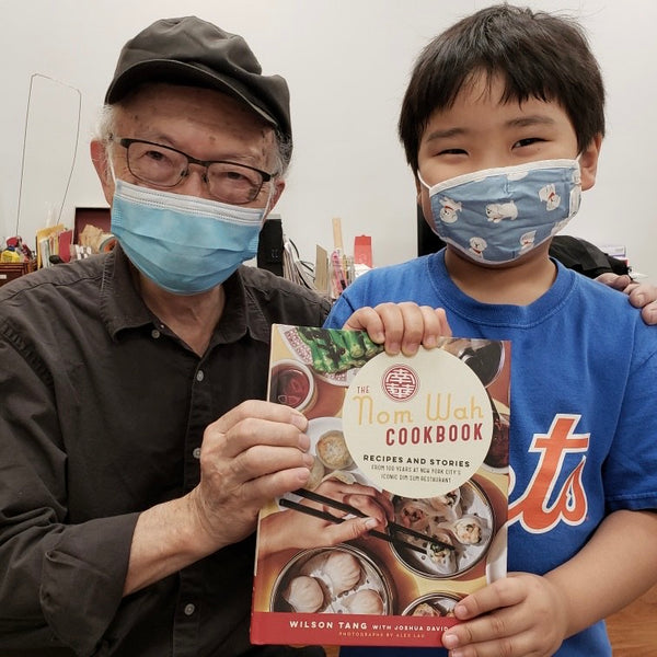Mr. Chen and Griffin holding the Nom Wah cookbook