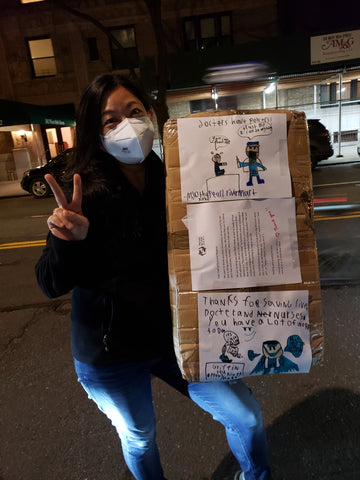 Woman wearing mask and holding large box