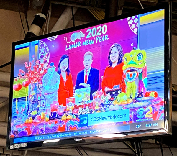 TV screen with Joanne Kwong, John Elliott, and Cindy Hsu live on CBS