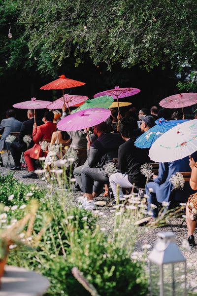Guests at an outdoor wedding with colorful parasols