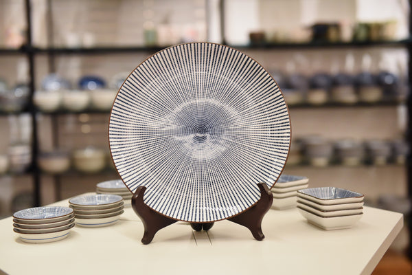 A blue and white striped plate on a plate stand