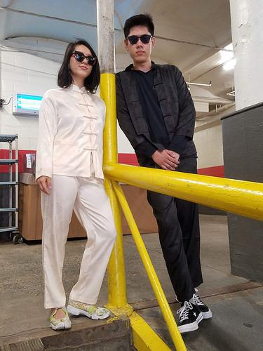 A young woman wearing sunglasses and white pajama outfit, and a young man wearing a black pajama outfit