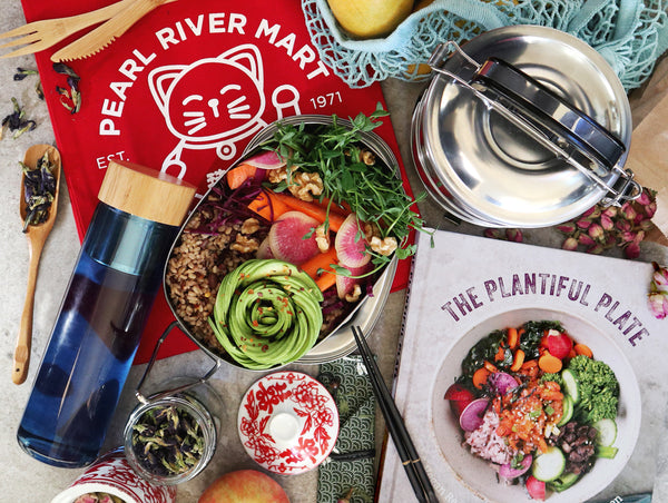 An array of earth-friendly items, including red reusable lucky cat tote bag, tin lunch tiffins, water bottle, travel chopsticks, as well as Plantiful Plate cookbook