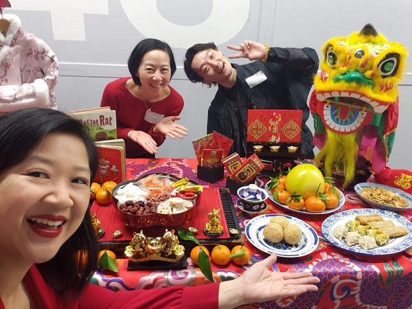 Pearl River staff with Joanne Kwong and table of Lunar New Year decor and foods