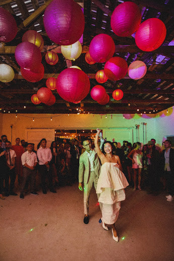 The bride and groom dance under lanterns