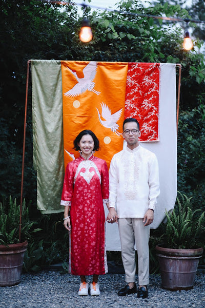 Vicki Ho and husband Todd pose in front of beautiful brocade fabrics.