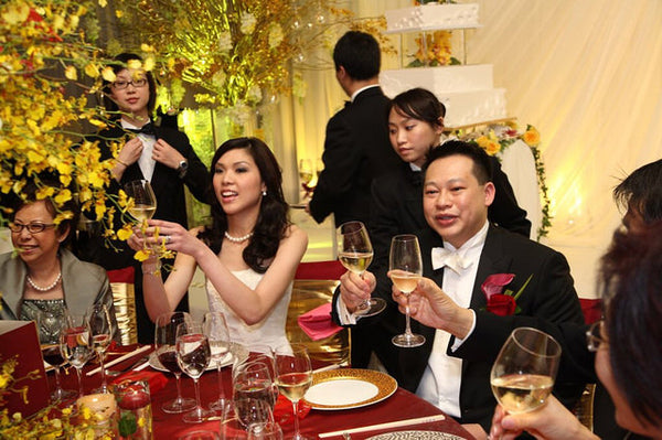 A bride and groom toast their guests