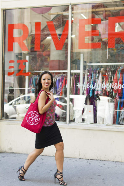 Young woman with red lucky cat tote bag walking past Pearl River Mart