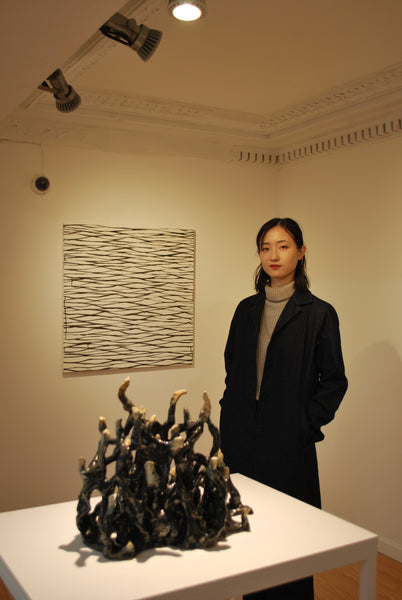 Artist Yingqian Cao posing by her abstract sculpture