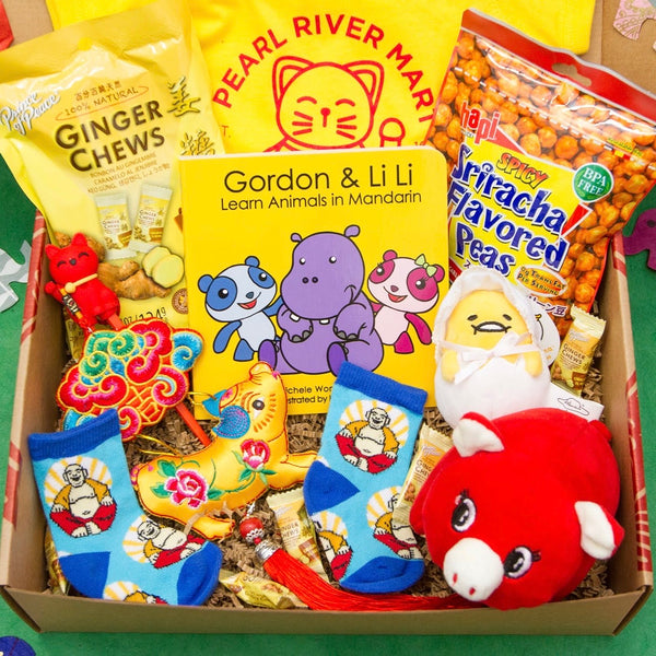 Gift box full of cute baby items, including yellow and red lucky cat onesie, a Gordon and Li Li Chinese book, a red plush pig, a Gudetama keychain, baby socks, a brocade pig ornament, and snacks for the parents
