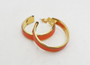 Close up of orange leather and gold-plated hoop earrings