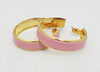 Close up of pink leather and gold-plated hoop earrings