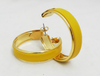 Close up of yellow leather and gold-plated hoop earrings