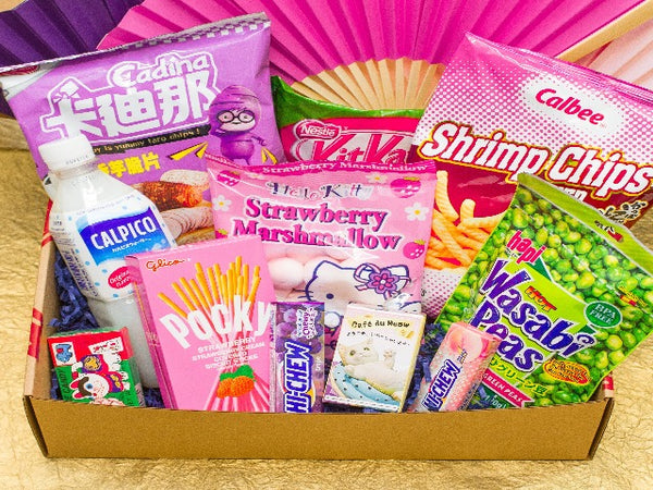 Box full of yummy Asian snacks, including taro chips, shrimp chips, Hello Kitty marshmallows, Pocky, Wasabi peas, Hi Chew, Kit Kats, and more