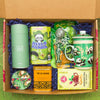 A box of tea lover items, including a canister of high quality green tea, matcha panda cookies, tin of jasmine tea, matcha candy, a mug, a handheld tea strainer, and ginger tea