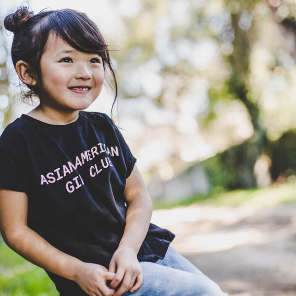 Little girl in black T-shirt with pink lettering, Asian American Girl Club