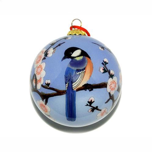 Holiday ornament with blue bird on the branch of a cherry blossom tree