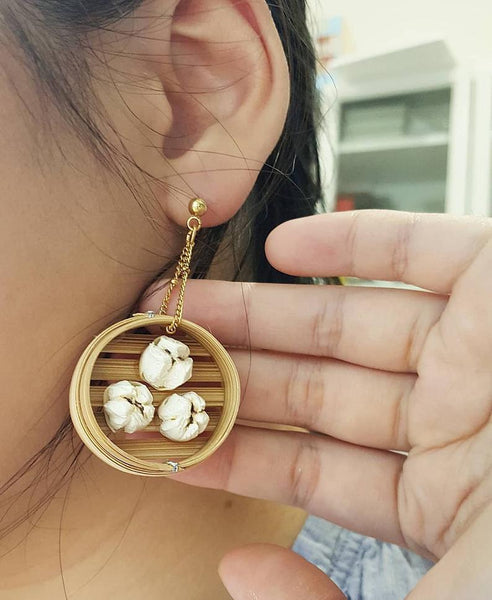 Woman wearing yummy pork bun earrings in a steamer basket