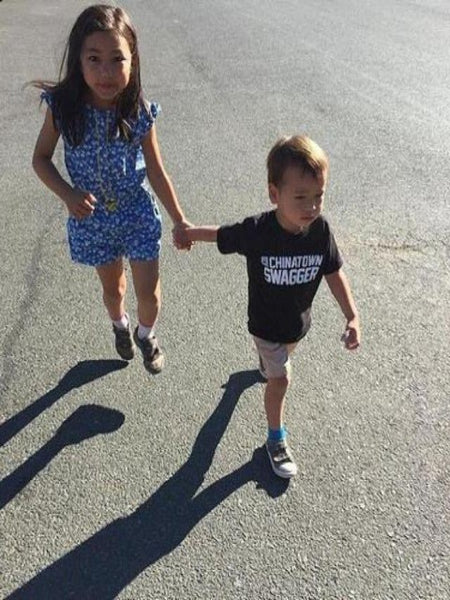 Little girl in a dress with a little boy wearing a cool black Chinatown Swagger T-shirt