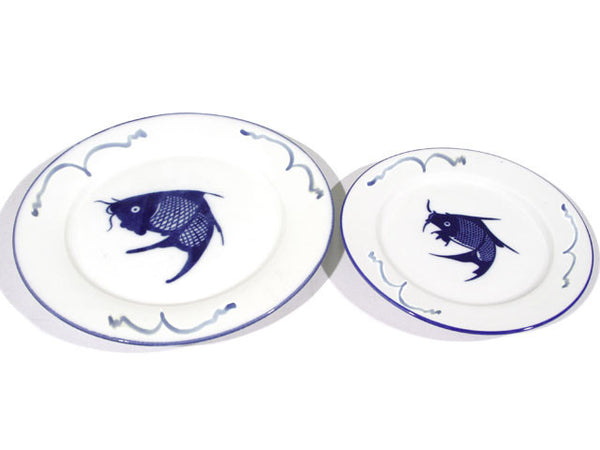 Two vintage porcelain plates, left plate larger than the plate on the right. Both sport the classic blue carp design in the center and contour waves on the rim with hand painted quality