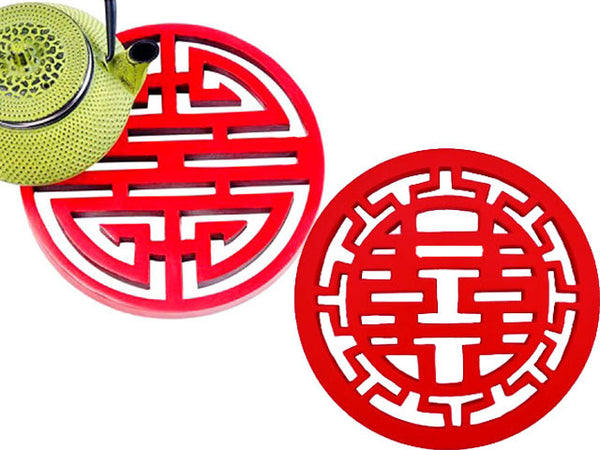 Two red cinnabar trivets with the Chinese characters for longevity (left) and double happiness (right)