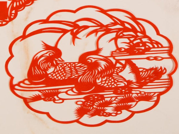 Red paper cut decoration with pair of mandarin ducks in water