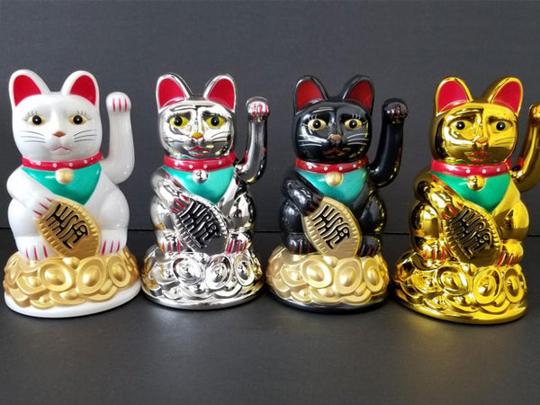 Four retro chic Japanese beckoning cats in white, silver, black, and gold