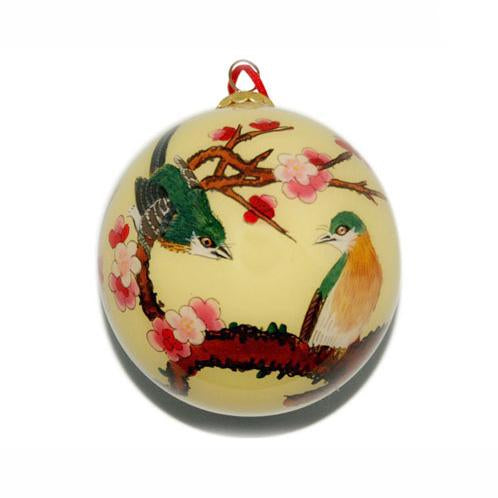 Holiday ornament with green and yellow birds on a branch of pink cherry blossoms