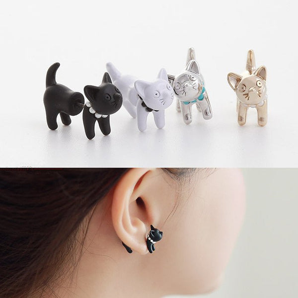 Cute cat earrings in black, white, silver, and gold. Woman wearing black cat earrings.