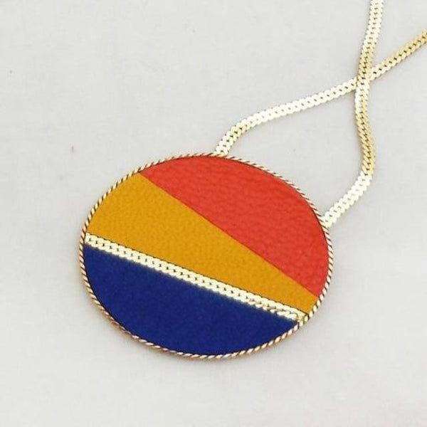 Close up of orange, yellow, and blue disk leather and gold-plated necklace