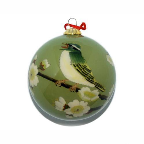 Holiday ornament with a singing spring bird on a white-blossomed-branch.