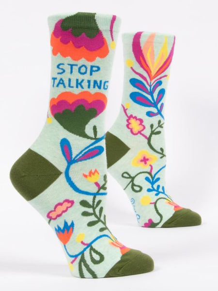Colorful socks with a floral pattern and the text stop talking