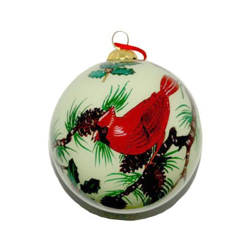 Holiday ornament of a bright red cardinal perching in a pine tree