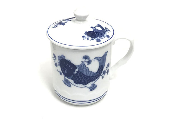 Two playful blue carps designed on a ceramic mug with lid and a Chinese stamp on the body of the mug for a vintage feel