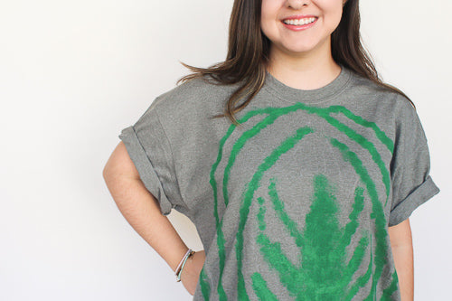 woman smiling showing close up of her shirt which has a watermelon peperomia leaf painted on oit