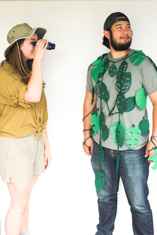 a woman and man standing next to each other. the woman is wearing safari gear and looking thru binoculars at the man, who is dressed in a green shirt and jeans and draped with strings felt of tropical foliage