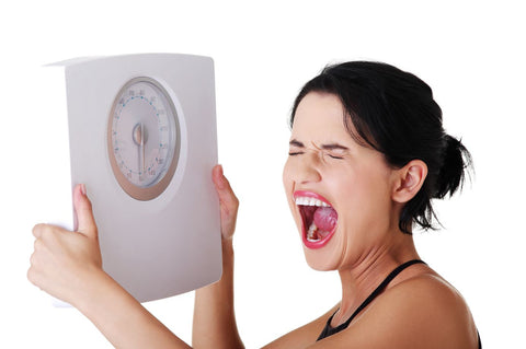 Screaming woman holding weighing scales
