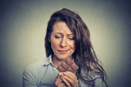 Woman looking concerned holding a chocolate bar