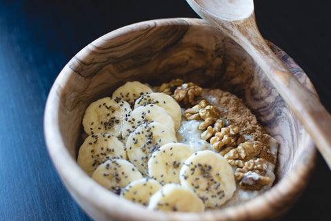 Wheat free oats in a bowl with cinnamon, bananas, walnuts & chai seeds