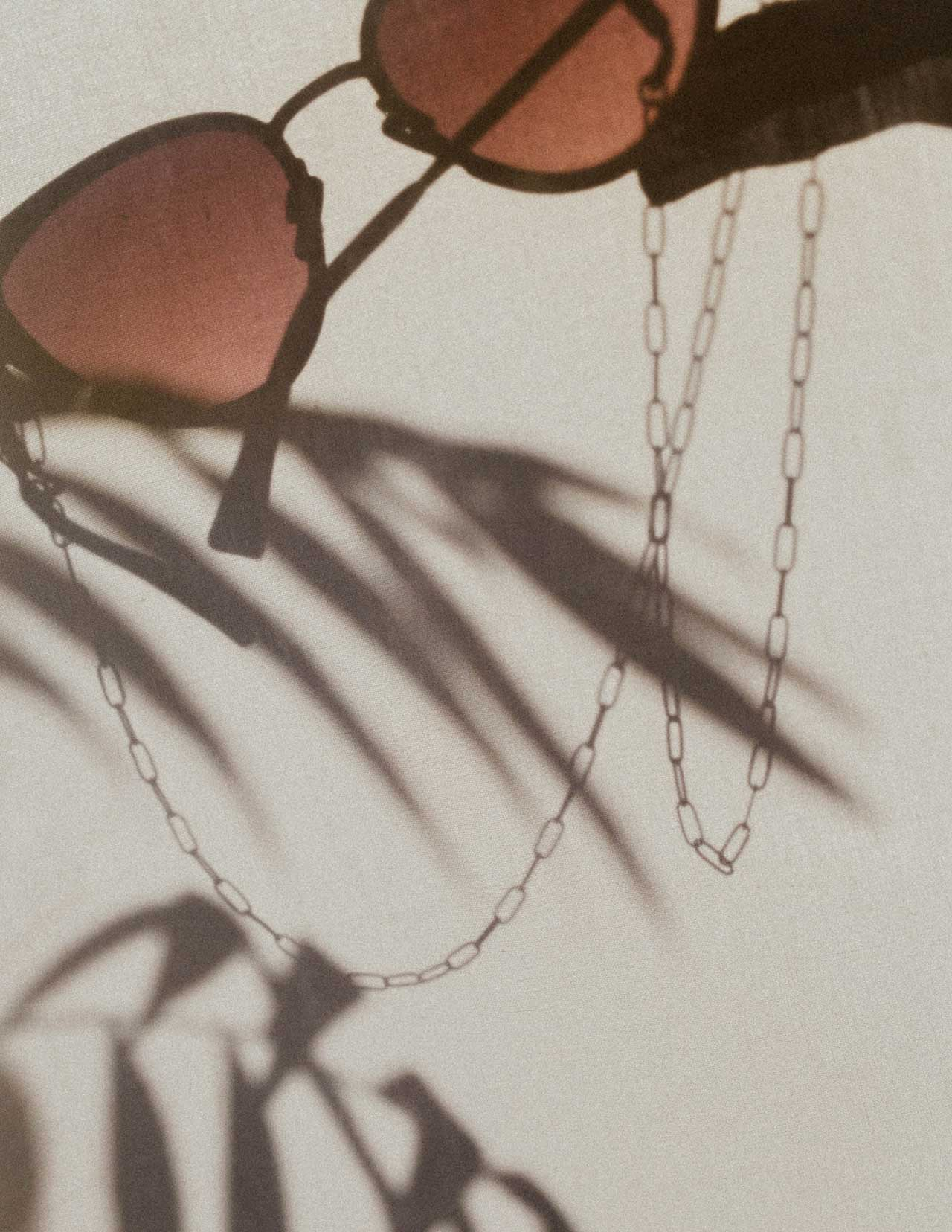 Shadow of sunglasses and KNOK Glasses Chain held up in the sun