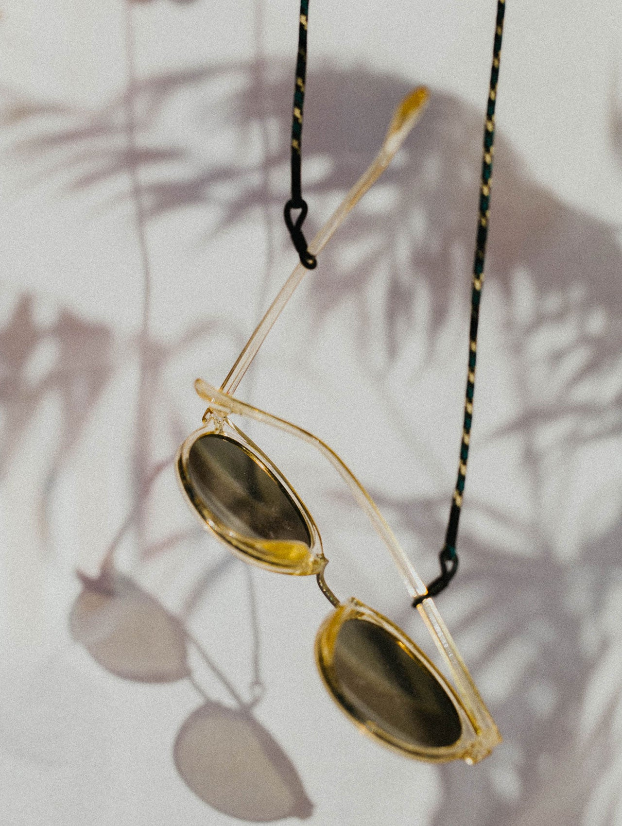 KNOK Glasses Chain Camo Green cord with sunglasses hanging in sunshine and palm shadows