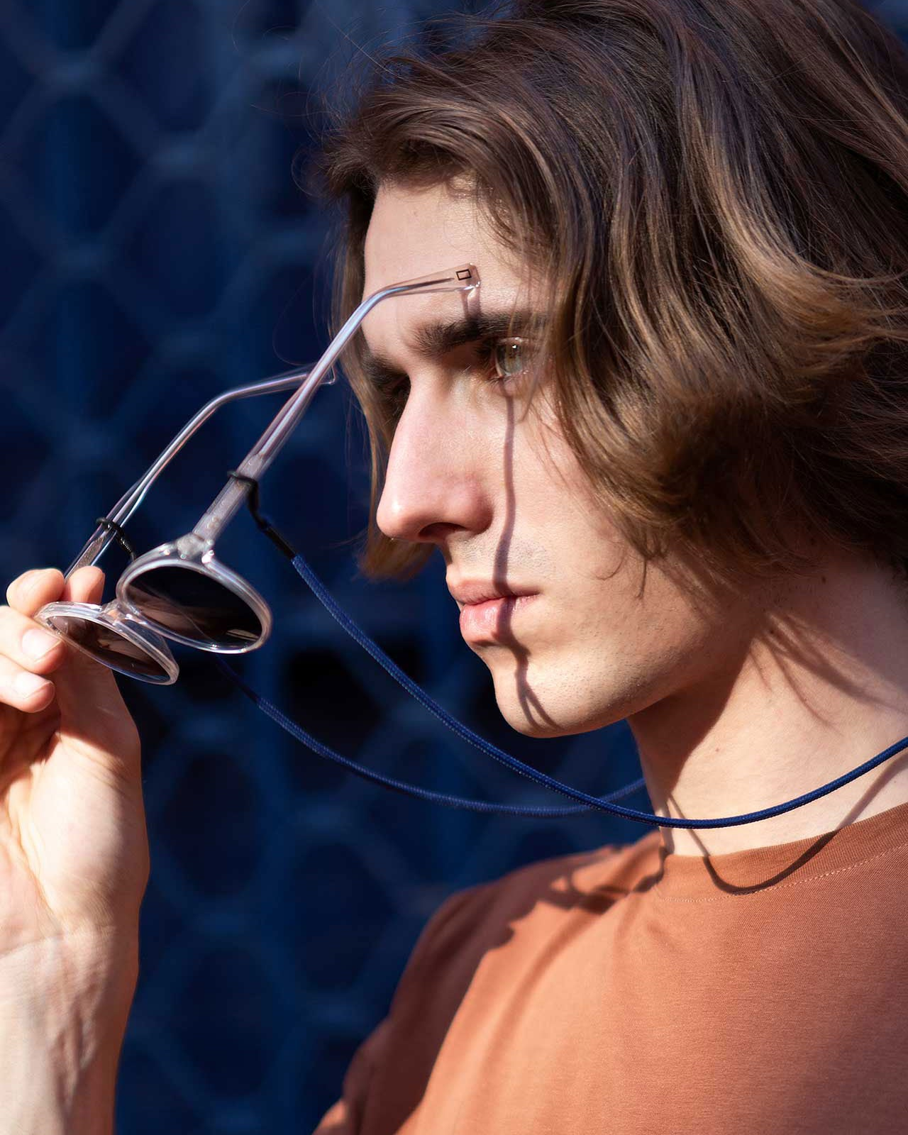 A model takes off clear sunglasses with KNOK Glasses Chain in Navy Blue attached