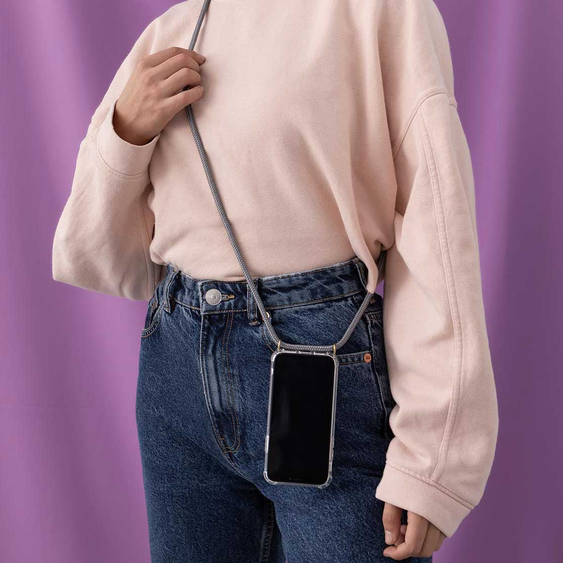 Model is wearing a Grey KNOK CASE Custom phone necklace, standing in front of a lilac background