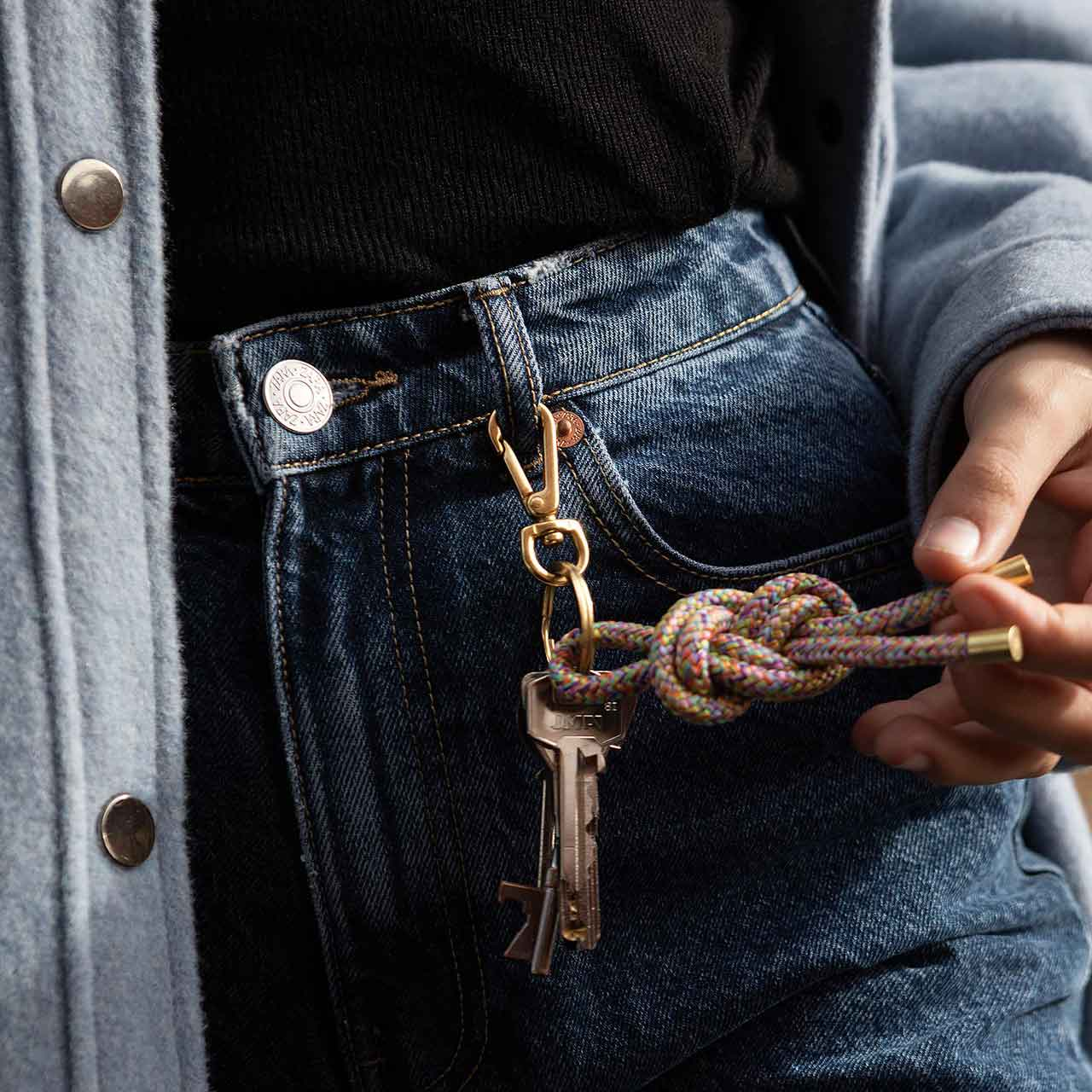 Model with a KNOK Key Knot keyring in multicoloured unicorn colour way attached to her jeans belt loop.