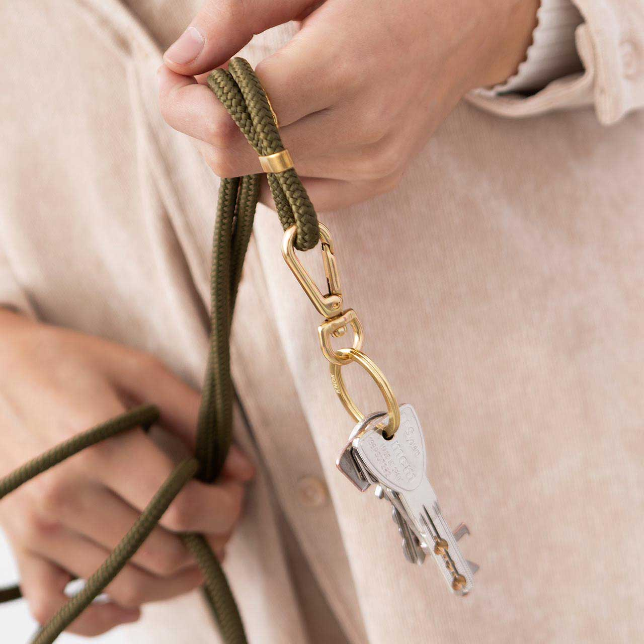 Model holding keys on a KNOK Key Holder in olive green