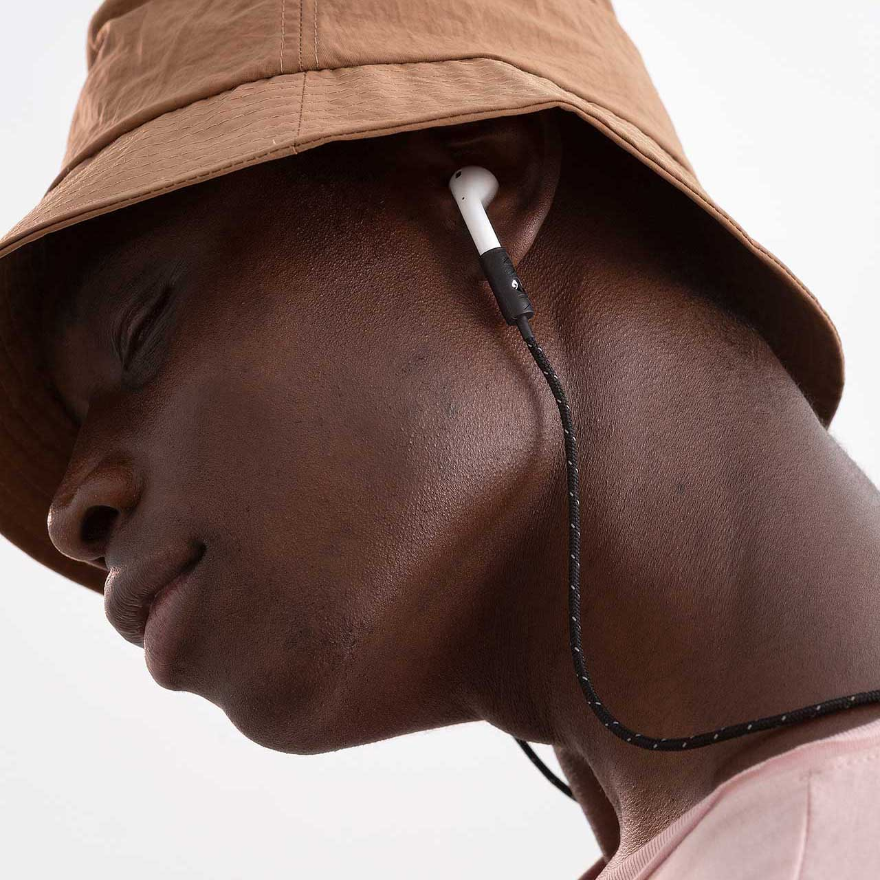Model wearing AirPods with KNOK AirPods Strap in Black Reflect