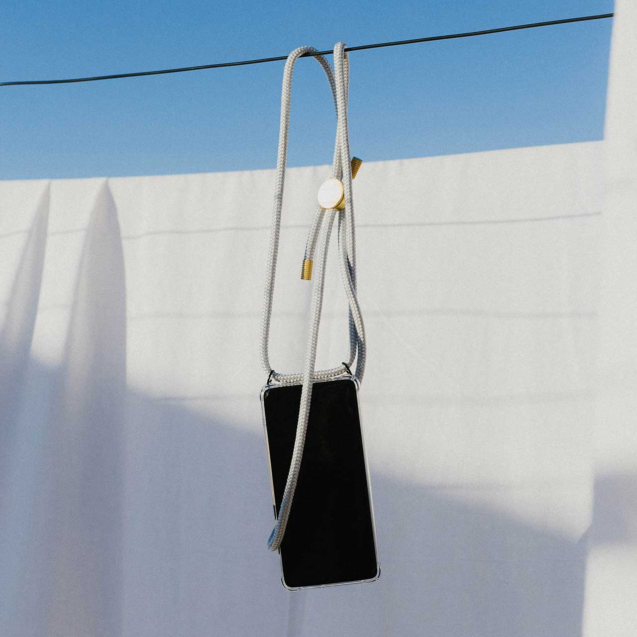 KNOK CASE phone necklace in silver grey hanging from a washing line in the sunshine