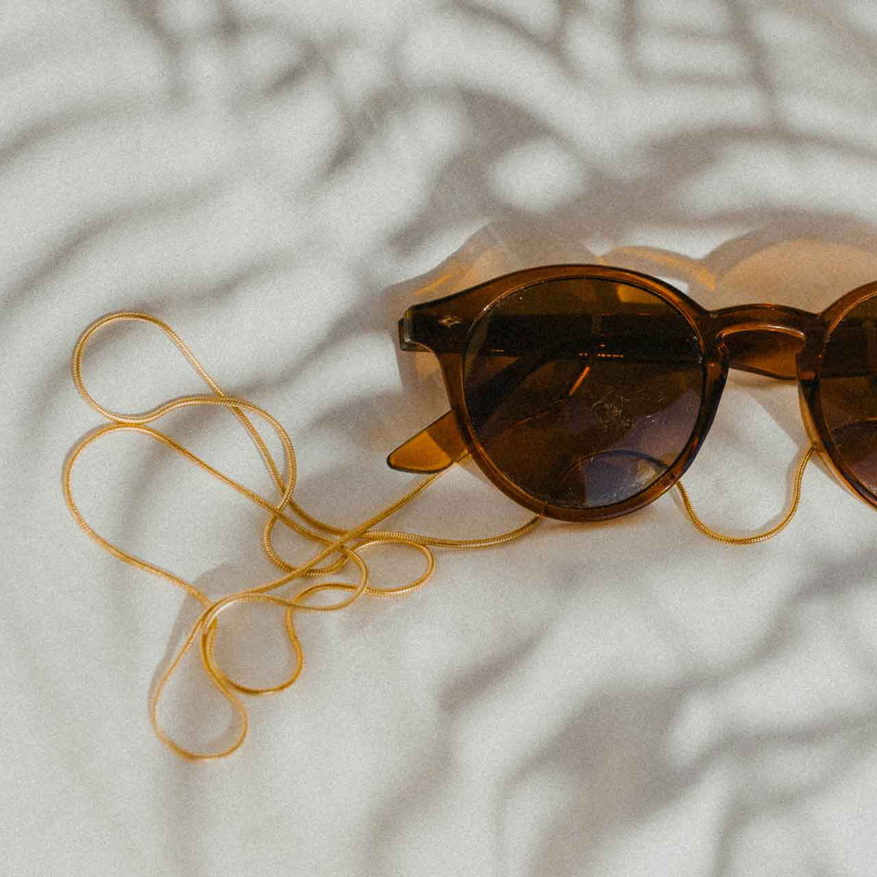 KNOK Baem Glasses Chain in gold shown on sunglasses with shadows of palm trees