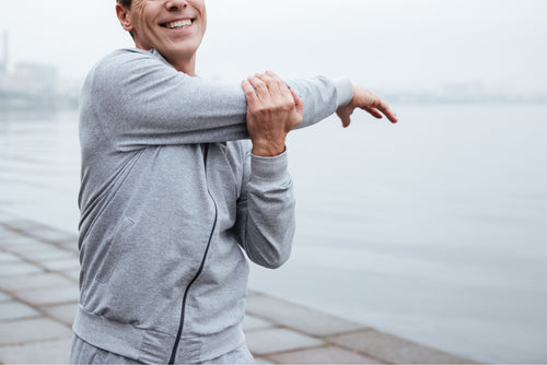White man in gray sweatshirt stretches before a run in front of a body of water